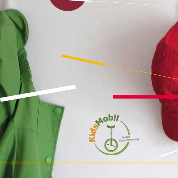 Ein grüner Pullover, eine braune Jacke und eine rote Mütze hängen an der Wand.