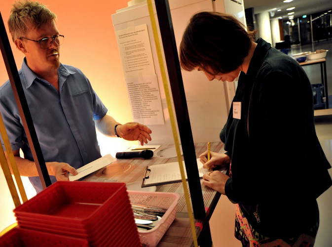 "Two people interacting with the Installation ""Abendbrot-Kongress"": one of them signing a form."