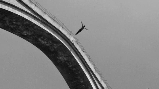 Sprung von einer Brücke in Grautönen