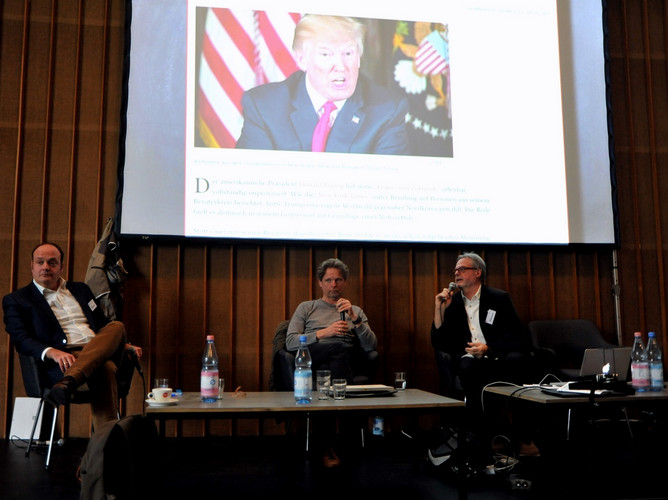 Presentation with three People on stage with a Picture of Donald Trump.
