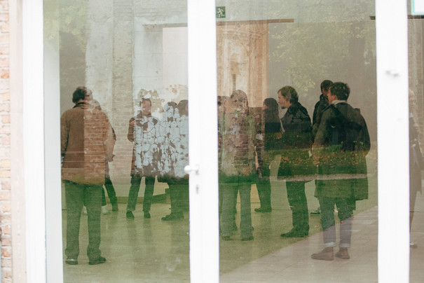 People in an exhibition room photographed through a reflecting glass door.