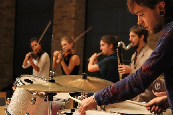 Ensemble aus Geige, Flöte, Bassklarinette und Schlagezug spielt.