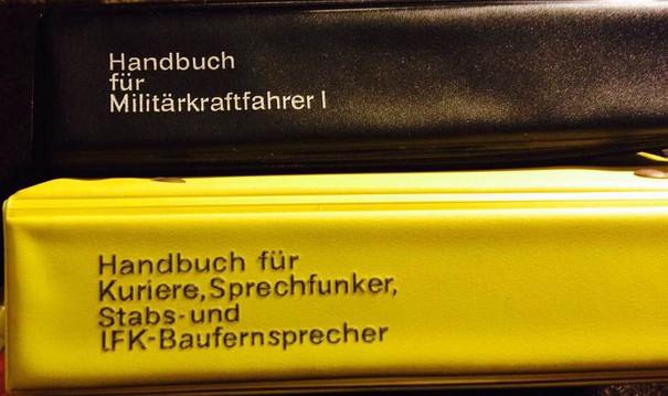 """Schwarzer Buchrücken vom """"Handbuch für Militärkraftfahrer I"""" auf gelbem Buchrücken vom """"Handbuch für Kuriere, Sprechfunker, Stabs- und IFK-Baufernsprecher""""."""