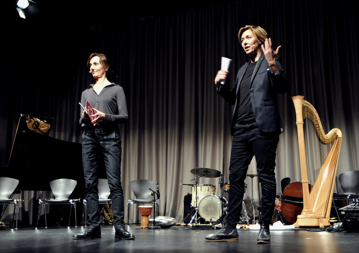 Two People on stage with microfone in front of Musical Instruments.