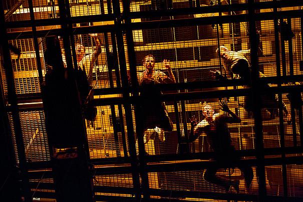 Vier Menschen, die auf einem Gitter stehen beziehungsweise liegen. Teil von Wunderland.