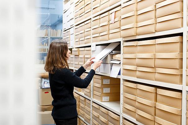 Eine Frau die aus Kästen in einem Archiv Seiten herausnimmt.