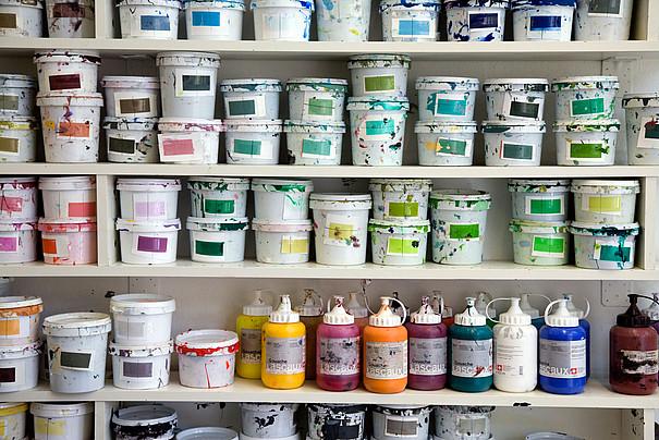 Ein Bild mit vielen Farbcontainern und Farbeimern.