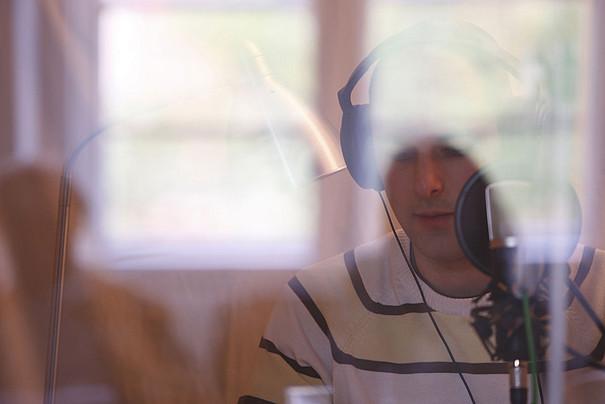 Ein junger Student steht vor einem Mikrofon und hat Kopfhörer auf.