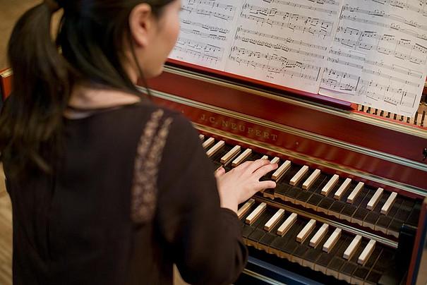 Eine junge Frau spielt auf einem Cembalo.