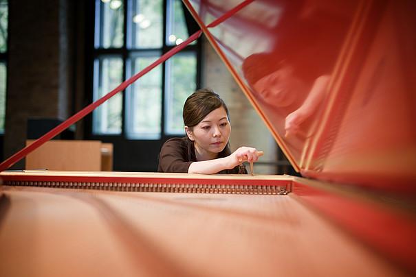 Eine Junge Frau stimmt ein Klavier