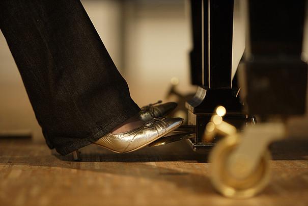 Damenfüße auf den Pedalen eines Klaviers