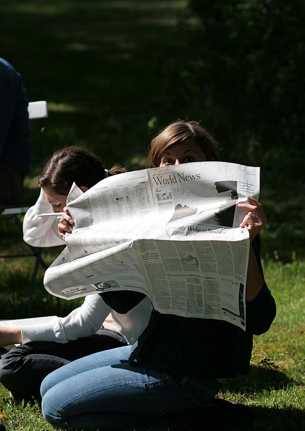 Eine Studentin hält eine Tageszeitung vor ihr Gesicht.