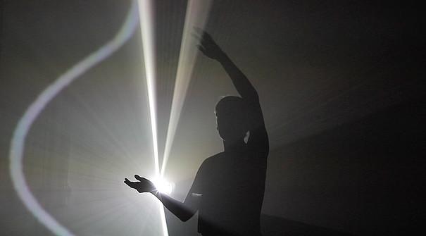 Ein Mann steht vor einem hellen Licht, man sieht nur seine Silhouette.