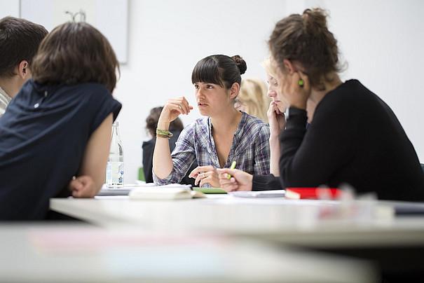 Fünf Personen in einer Beratungsrunde an einem Tisch.