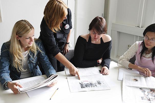 Mehrere Frauen sitzen an einem Tisch und lesen Zeitung.