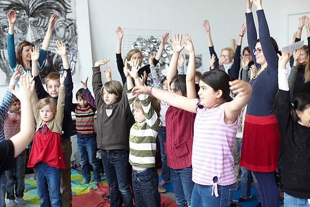 Eine Gruppe kleine Kinder heben ihre Hände aus Freude in die Luft.