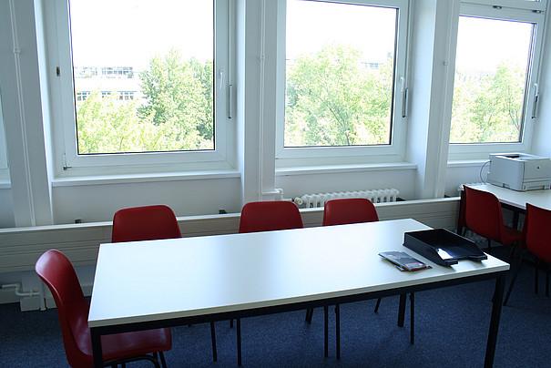 Tisch, um den leere Stühle gruppiert sind.