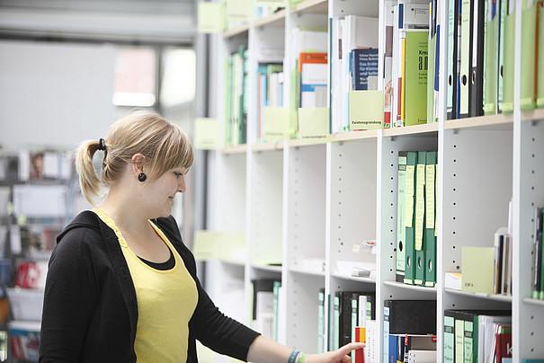 Eine Studentin vor einem Regal.