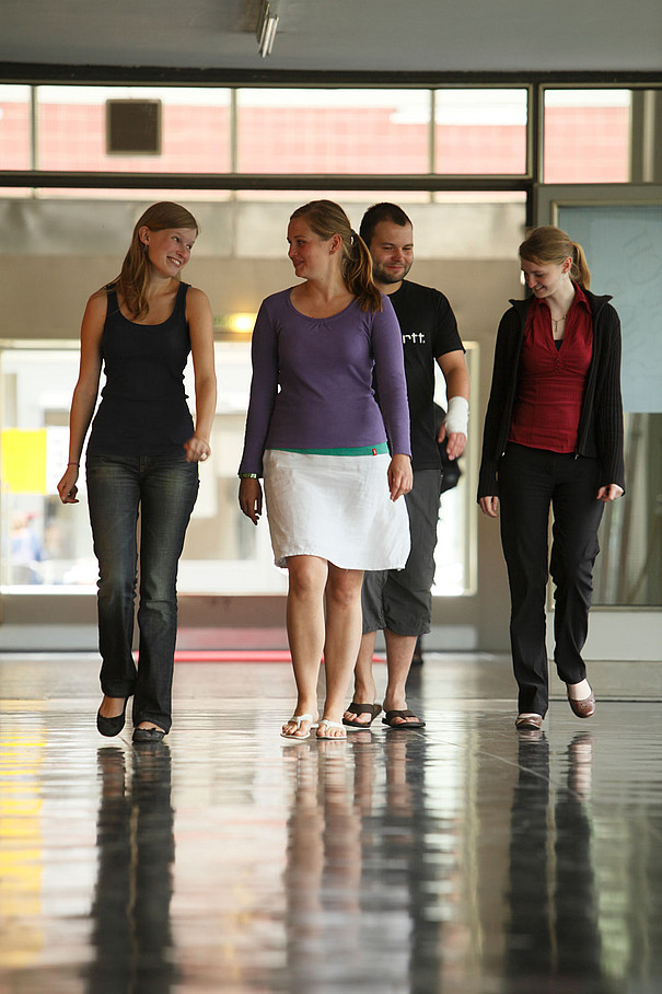 Drei Frauen und ein Mann laufen in einem Gang der Universität der Künste.