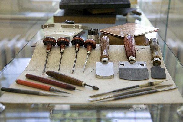 Verschiedene Werkzeuge aus der Druckwerkstatt der Faklutät Bildende Kunst liegen auf einem Tisch.