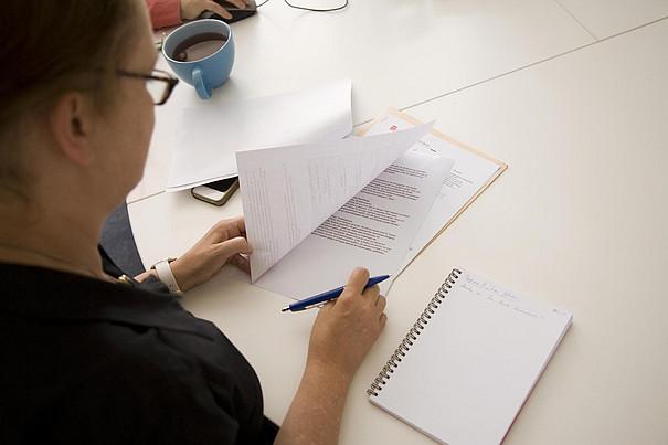 Eine Mitarbeiterin macht sich Notizen zu einem ausgedruckten Papier.