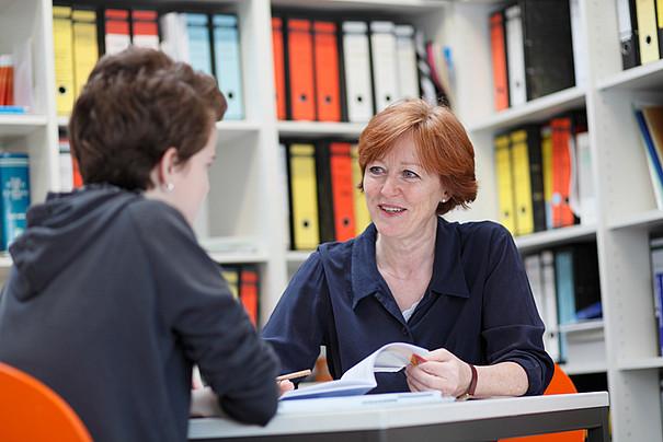 Zwei Frauen in einer Gesprächssituation in einem Büro.