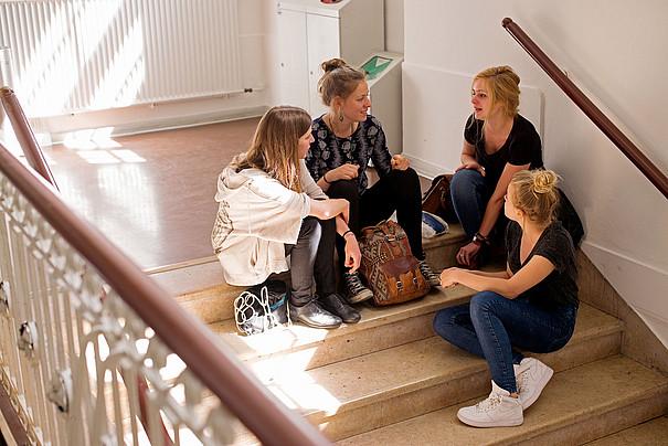 Eine Gruppe Studentinnen sitzt auf Treppen.