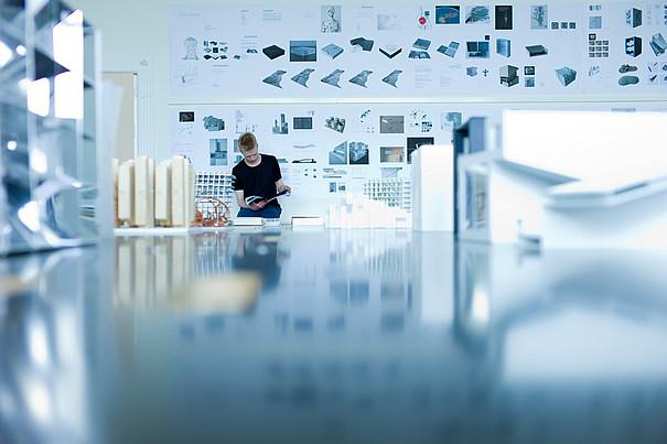 Ein Student steht in einer Kunstwerkstatt und liest ein Heft.