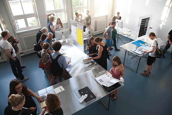 Innenaufnahme mit Menschen, die sich ausgestellte Printprodukte ansehen.