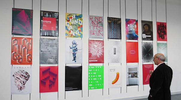 Der Präsident Martin Rennert betrachtet eine Reihe von Plakaten, die an der Wand hängen.