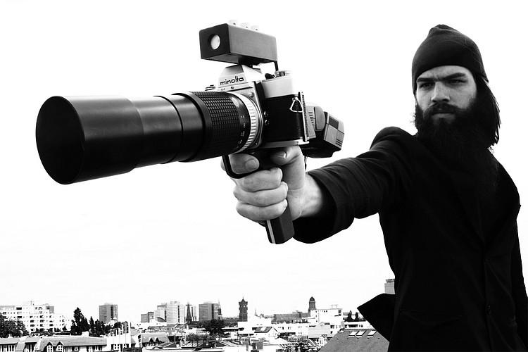 Eine Person, die eine Kamera mit einem Riesenobjektiv wie eine Schusswaffe hält.