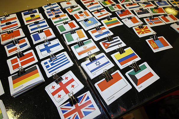 Kleine Flaggen aus verschiedenen Ländern auf einem Tisch.