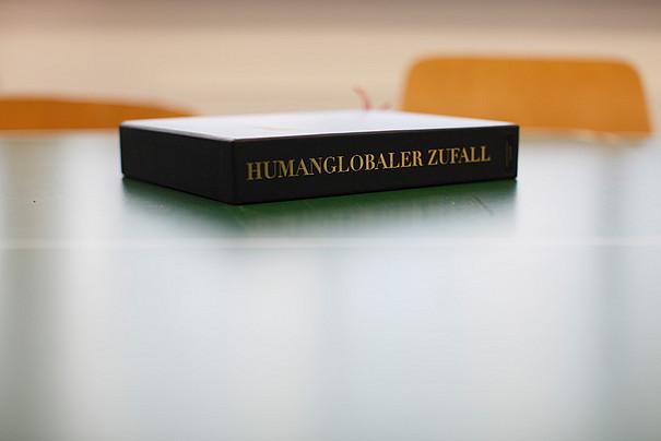 Eine kleine, schwarze Schachtel, auf der Humanglobaler Zufall steht.