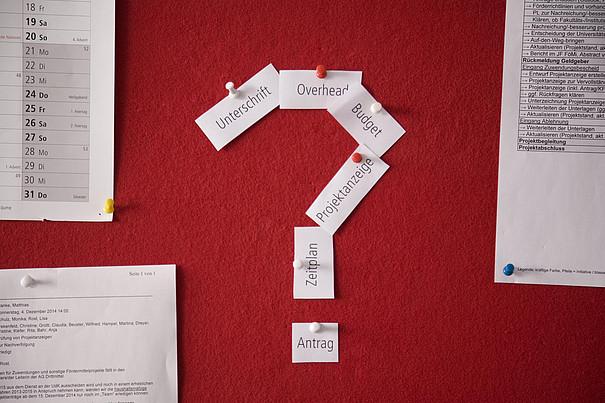 Eine rote Pinnwand mit Notizen und einem Teil eines Kalenders