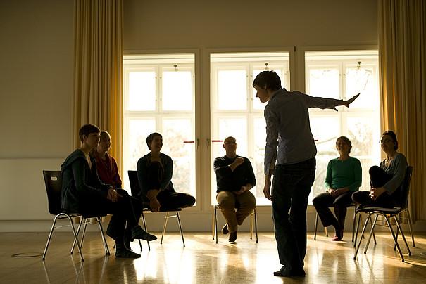 Ein Erzähler präsentiert lebhaft eine Geschichte vor einer Gruppe in einem Stuhlkreis.
